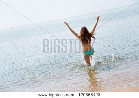 Happy young woman runs into the warm sea