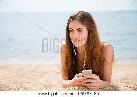 Young woman uses a smartphone, lying on the beach