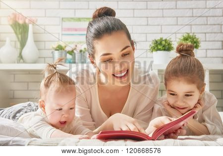 pretty young mother reading a book to her daughters