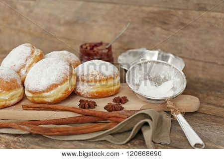 Delicious sugary donuts with spices on wooden background