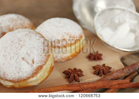 Delicious sugary donuts with spices on wooden cutting board closeup
