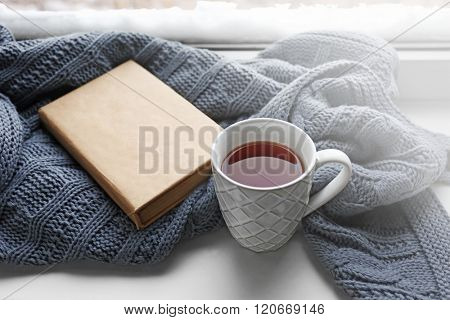 Cup of tea, book and warm knitted plaid on windowsill, close up