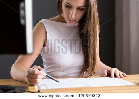 Beautiful Woman Looking At Contract At The Desk