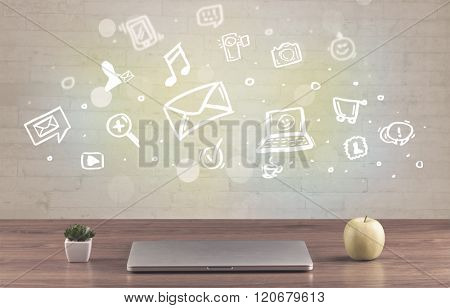 Social media online communication concept with icons and close up of business office desk full of work equipement