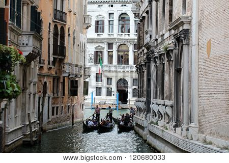 VENICE ITALY - SEPTEMBER 22, 2015: Three splendid gondola sculling on delightful romantic authentic pure venetian narrow old street with amazing historical vintage buildings outdoor horizontal picture