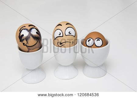 Three Eggs With Frightened Face In Eggcup