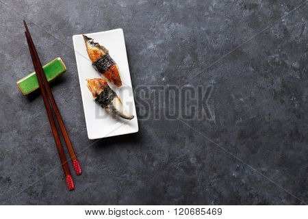 Set of unagi sushi and chopsticks on stone table. Top view with copy space