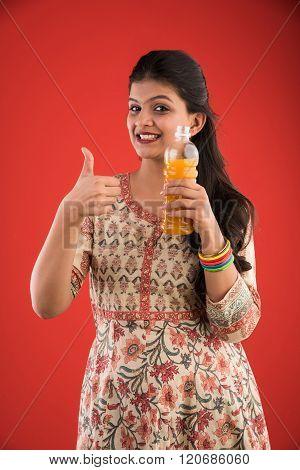 indian pretty girl with orange or mango juice bottle,