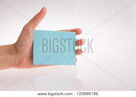 Hand holding a light blue color rectangular paper on a white background