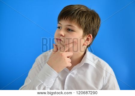 Pensive teenage boy on a blue background