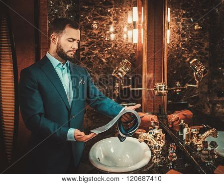 Confident well-dressed man choosing a tie in luxury bedroom interior.