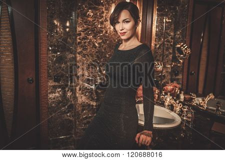 Beautiful well-dressed woman in luxury bathroom interior.