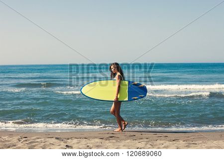 young woman prepare for surf on board full body shot on sandy beach by the sea