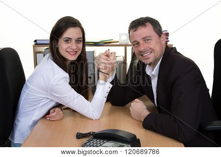 A Man And Woman With Hands Clasped Arm Wrestling At Office
