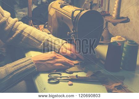 Man works on sewing machine.