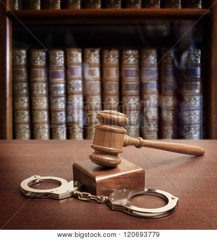 Gavel and handcuffs on wooden background