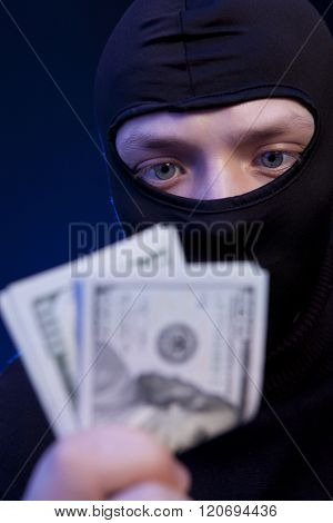 Thief. Man in black mask holding the money