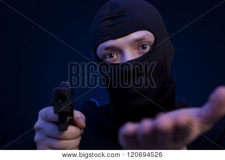 Man holding gun over dark blue background