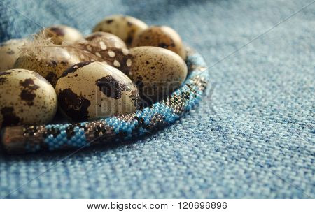 Easter composition with feather quail eggs and beaded jewellery on woolen fabric. Close up.