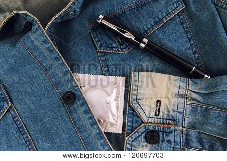 Condom and pen in the vintage blue jeans pocket. Focus on the condom.