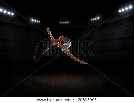 Young girl engaged art gymnastic at sports hall