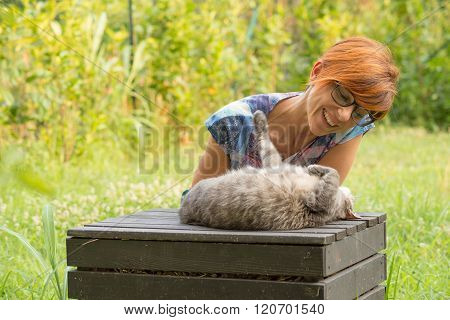 Woman Playing With Cat Outdoors In Green Home Garden