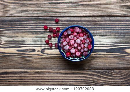 Fresh frozen cranberry in bowl over wooden rustic background, top view