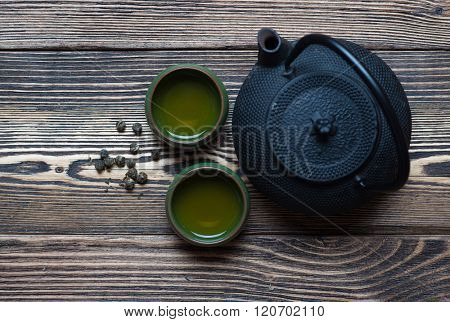 Tea composition with green ceramic tea cups and black iron teapot on dark wooden background