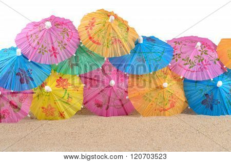 Colorful Paper Cocktail Umbrellas In Sand Close-up On A White