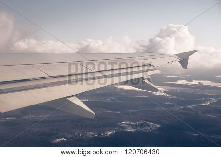 Wing and cloudscape. Clouds and sky as seen through window of aircraft