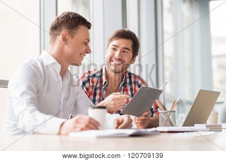 Positive men sitting at the table