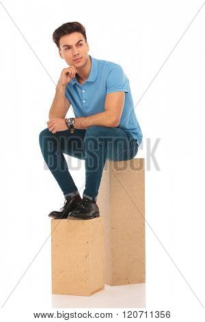 handsome man seated on wooden boxes in isolated studio background while thinking and looking away from the camera