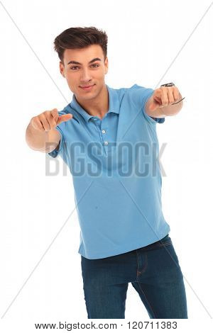 portrait of handsome young man in blue shirt pointing with both hands and looking at the camera in isolated studio background