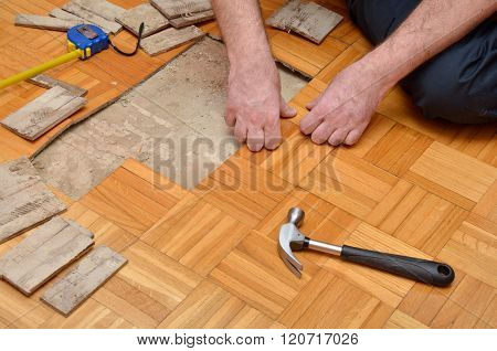 Man Removing Damaged Parquet In Apartment