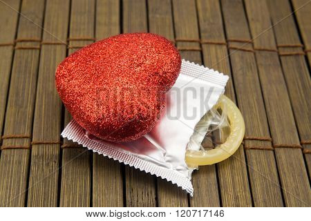 Red Heart And Condom On A Wooden Background