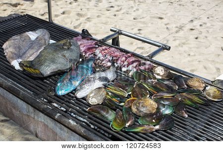 grilling seafood assortment of fish, shells of molluscs