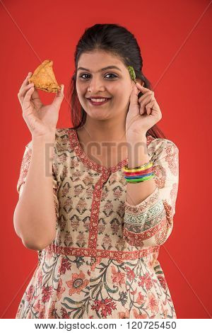 pretty indian young girl eating tasty samosa