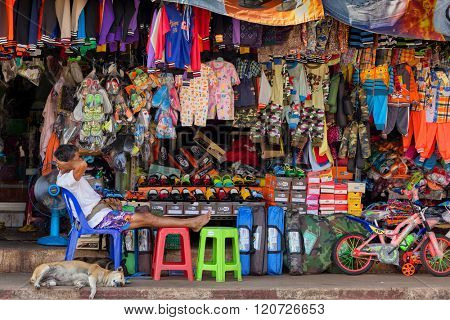 THONG PHA PHUM, THAILAND, JANUARY 23, 2016 : A man and his dog are lying asleep under the heavy sun in the street clothes store in Thon Pha Phum, Thailand