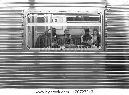 People Sitting In A Subway Car Seen Through Window.