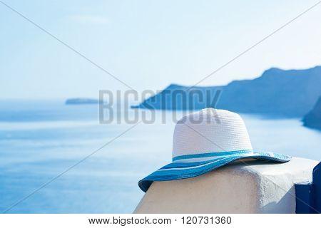 Sun hat on white stone wall on Santorini island, Greece. View on Caldera and Aegean sea from Oia. Travel, tourist, tourism concept