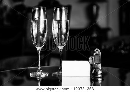 Full champagne glasses, antique keys and blank white card. Luxury hotel apartment, room service concept. Vintage, retro.