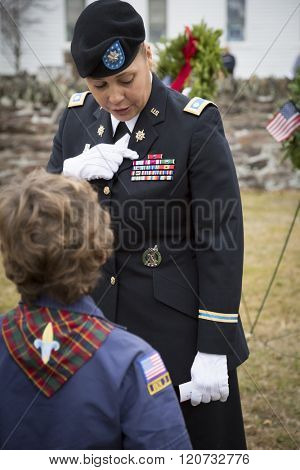 SUCCASUNNA, NJ-DEC 12, 2015: U.S. Army Lt. Col. Ingrid Parker from Picatinny Arsenal talks to a Cub Scout about her service ribbons after the ceremonial wreath laying for 2015 Wreaths Across America.