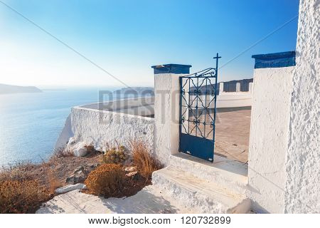 Gate to a church in Fira on Santorini island, Greece. Caldera view, Aegean sea.