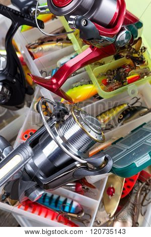 Fishing Reel On Boxes With Lures And Wobblers