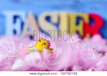 closeup of a yellow toy chick surrounded by soft pink feathers and three-dimensional letters forming the word easter in the background, against a blue background