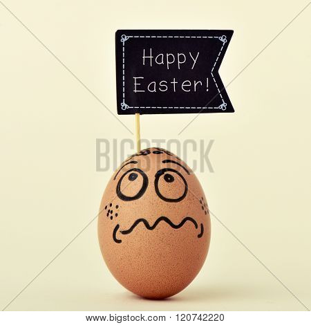 a brown egg ornamented with a funny face with a black flag-shaped signboard with the text happy easter, on an off-white background