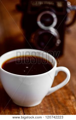 closeup of a cup of coffee and an old camera on a rustic wooden surface