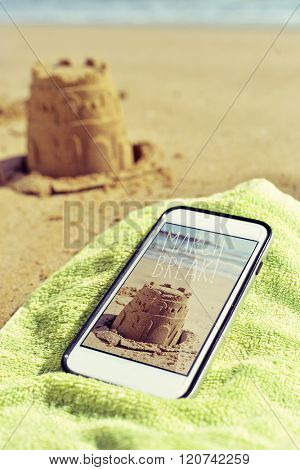 a smartphone with a picture shot by myself of a sandcastle and the text march break in its screen, placed on a green towel on the sand of a beach and the depicted sandcastle in the background