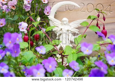 Grave angel between flowers in front of grave stones