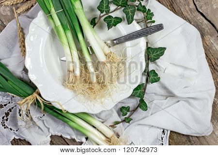Organic spring onions on plate